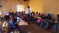 Viele junge Menschen sitzen an Tischen während des IT Unterrichts